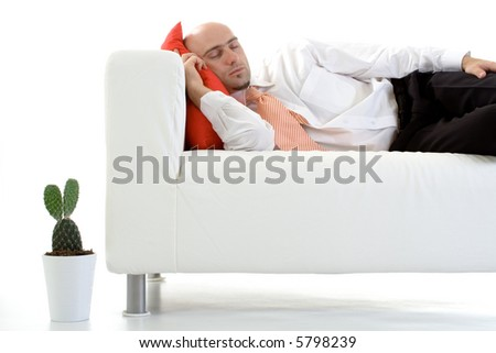 A young executive lying down on the couch, taking a nap. - stock photo