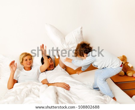 a young family is in bed in the bedroom