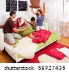 a young family is making a pillow-fight in their bedroom - stock photo