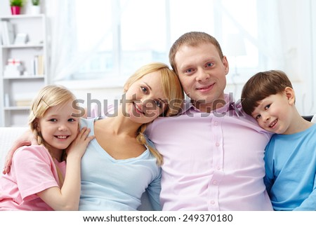 A young family of four looking at camera at home - stock photo