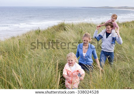 A young family of four walking through long grass next to the beach. They are wearing casual clothing and are smiling.  - stock photo