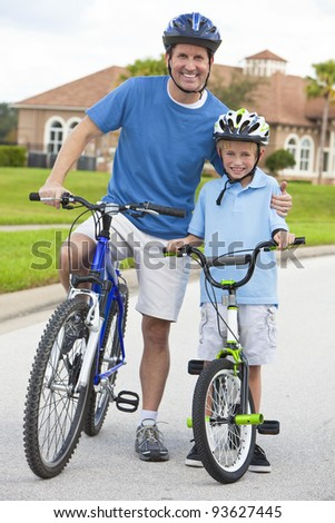 A young family of man and boy, father and one boy child, cycling together. - stock photo