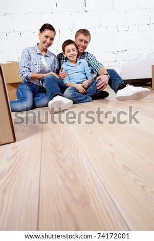 A young family of three sitting on the floor of new house