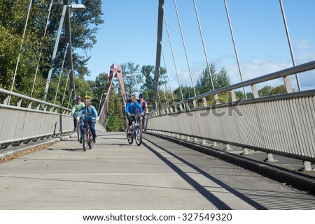 A young family rides across the Willamette River on the DeFazio Bike Bridge in Eugene Oregon - stock photo
