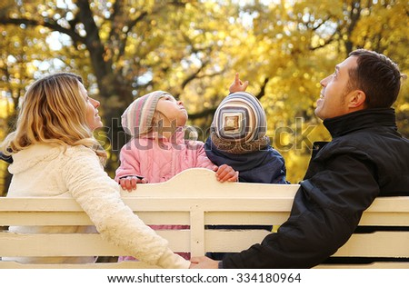 a young family sitting on a bench in the autumn park - stock photo