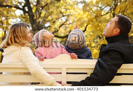 a young family sitting on a bench in the autumn park