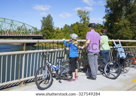 A young family takes a break on a bike bridge as they look up the river. - stock photo