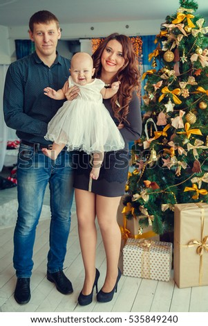 a young family with a baby near Christmas tree with presents.