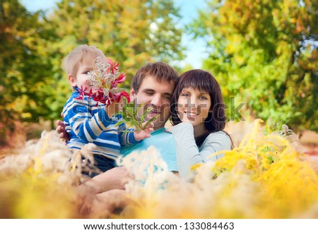 A young family with a baby on the nature in the long grass
