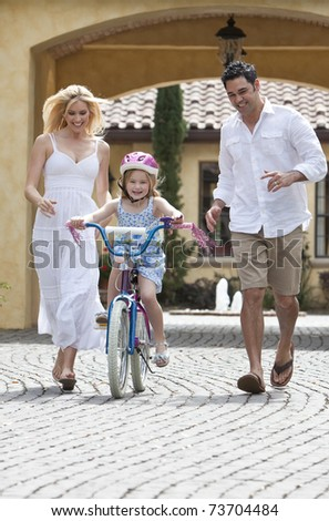 A young family with girl child riding a bicycle and her happy excited parents giving encouragement and running alongside her - stock photo