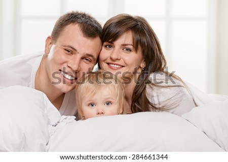 A young family with little daughter on bed in the bedroom on light window background - stock photo