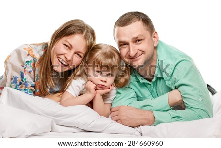 A young family with little daughter to bed on white background - stock photo
