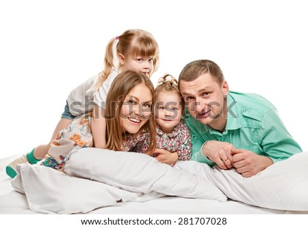 A young family with little two daughters to bed on white background - stock photo