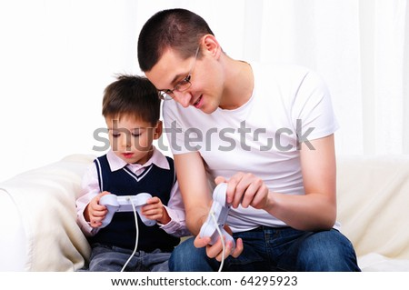 A young father and son together playing video games