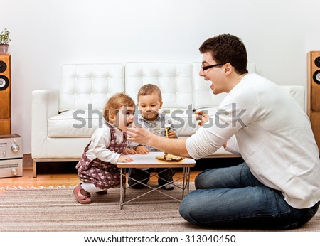 A young father feeding two little children - a boy and a girl at home. - stock photo