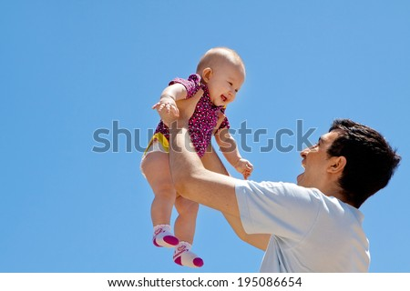 A young father playing with his precious little girl outdoors - stock photo