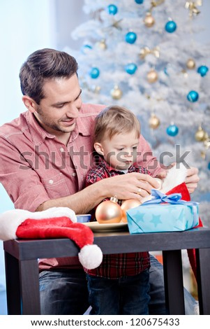 a young father with son at Christmas tree