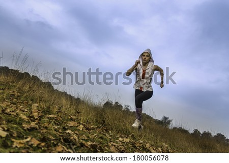 A young female athlete running through a park. / Young female athlete running in park - stock photo