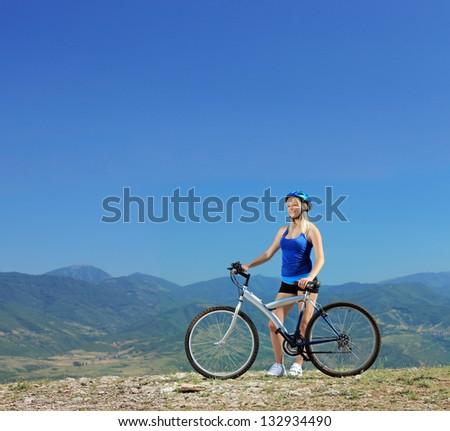A young female biker posing with a mountain bike outdoors - stock photo