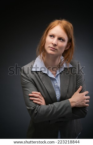 A young female business leader poses with folded arms before a dark studio background.