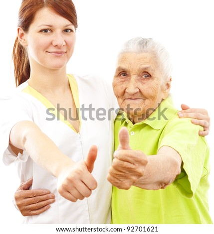a young female doctor and a very old woman showing thumbs up - stock photo