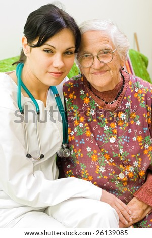 A young female doctor sitting next to an old woman.