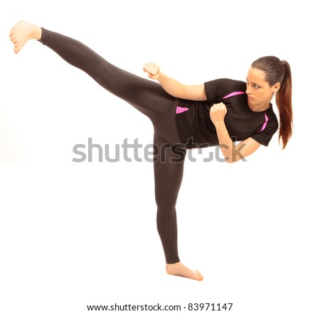 A young female dressed in gym clothes performing a martial arts kick on isolated white background