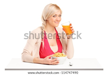 A young female drinking a juice and eating cornflakes at breakfast isolated on white background