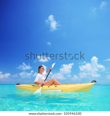 A young female in a yellow kayak kayaking near a Kuredu island, Maldives, Lhaviyani atoll - stock photo
