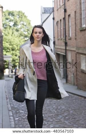 A young female looks at the camera as she walks along a cobbled city street. She is wearing a big winter coat and carrying her bag on her shoulder.