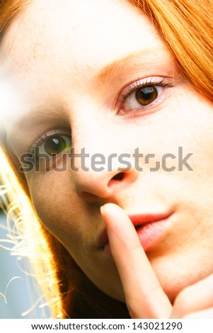 A young female making a sign to keep quiet. A closeup image with creative lighting.
