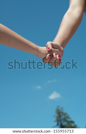 A young female person holding hands with an older female person close up outdoors