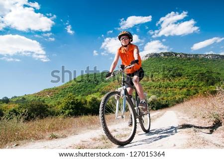 A young female riding a mountain bike outdoor - stock photo