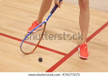 A young female squash player hiting a ball in a squash court