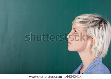 A young female student standing in front of the blackboard and looking at something. - stock photo