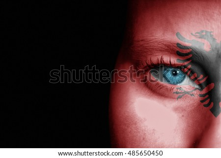A young female with the flag of Albania painted on her face on her way to a sporting event to show her support.