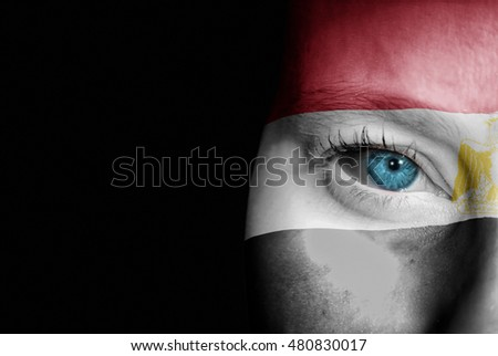 A young female with the flag of Egypt painted on her face on her way to a sporting event to show her support.