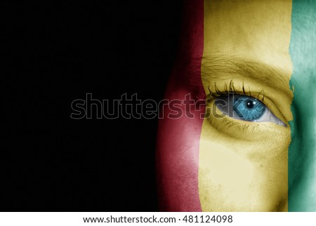 A young female with the flag of Guinea painted on her face on her way to a sporting event to show her support.