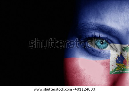 A young female with the flag of Haiti painted on her face on her way to a sporting event to show her support.