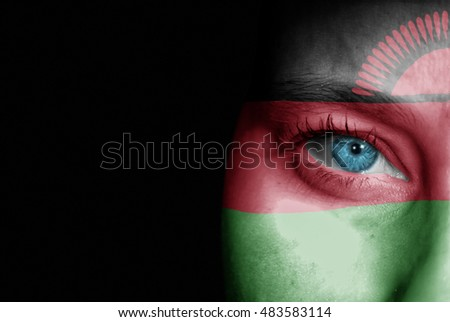 A young female with the flag of Malawi painted on her face on her way to a sporting event to show her support.