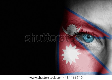 A young female with the flag of Nepal painted on her face on her way to a sporting event to show her support.