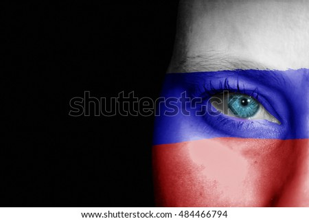 A young female with the flag of Russia painted on her face on her way to a sporting event to show her support.