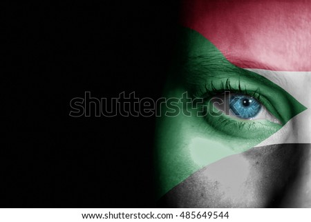 A young female with the flag of Sudan painted on her face on her way to a sporting event to show her support.
