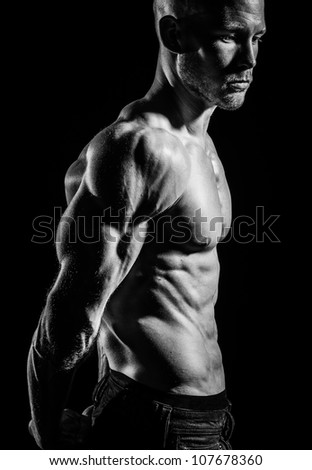 a young fit athlete posing his ripped body