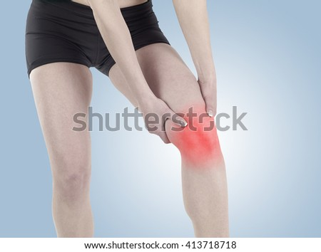 A young fitness woman massaging her painful knee. - stock photo