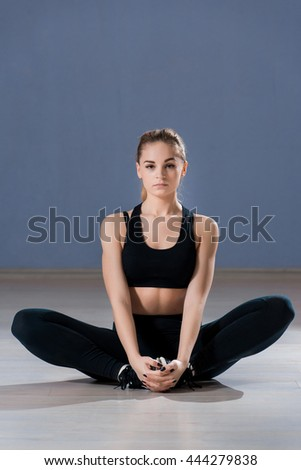 A young fitness woman sitting in a relaxed posture. Gorgeous blonde looking at the camera - stock photo