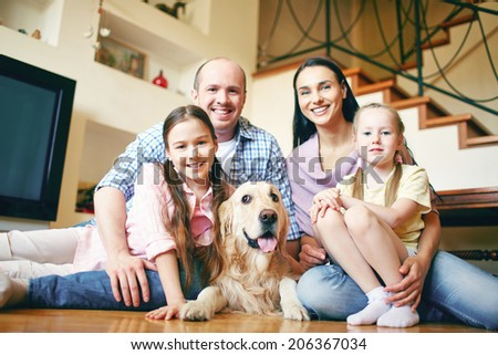 A young friendly family and their pet sitting on the floor and looking at camera at home - stock photo