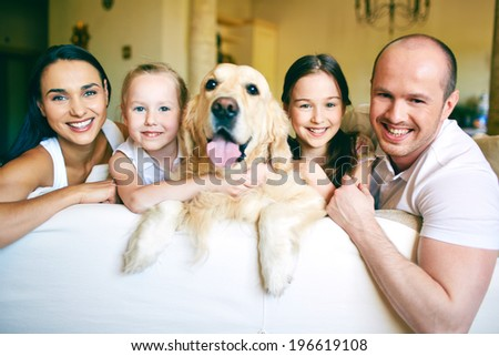 A young friendly family of four with pet looking at camera at home - stock photo