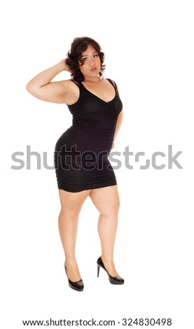 A young full size woman in a black dress with on hand on her head standing isolated for white background. - stock photo