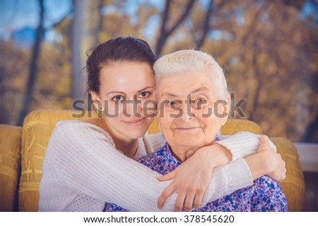 A young girl and an elderly grandmother. Girl hugging her grandmother. - stock photo